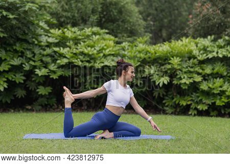 Portrait Of Happy Young Caucasian Woman Exercising Yoga Outdoors Early Morning. Beautiful Girl Pract