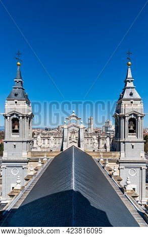 Madrid, Spain - March 20, 2021: The Roof And The Towers Of Almudena Cathedral Against Cityscape Of M