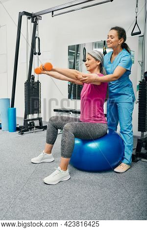 Mature Woman Doing Exercises Using Dumbbells And Fitness Ball With Her Physiotherapist At A Rehab Cl