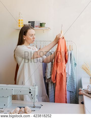 Young Female Dressmaker Or Fashion Designer Standing Near Her Workplace In Sewing Atelier With New B