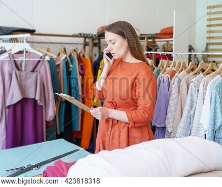 Young Businesswoman Owner Of Atelier Talking With Fabric Supplier On Cellphone While Working In Work