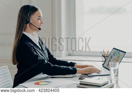 Attractive Businesswoman In Formal Suit Wearing Headset Having Video Call On Laptop Computer, Workin