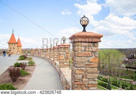 Street Lighting. Stone Fence With Towers. Fence Decorated With Facing Stone In The Park