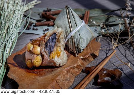 Chinese Rice Dumpling (zongzi) Shaped Pyramidal Wrapped By Leaves Ingredients On Wooden Plate And Ch
