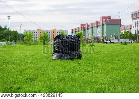 A Black Bag Made Of Thick Polyethylene, Stuffed With Grass, Stands On The Green Lawn In The Park