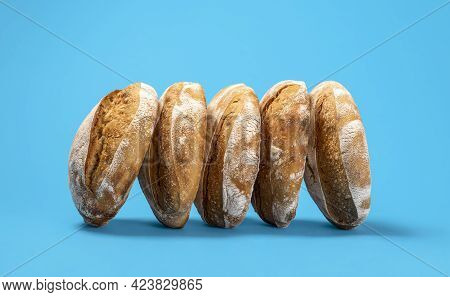 Delicious Sourdough Loaves Of Bread Isolated On A Blue-colored Background. Sideview With A Couple Of