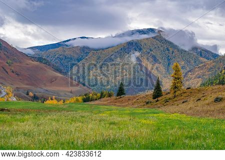 Landscape Of A Mountain Autumn Rocky Valley With Green Grass In A Clearing And Clouds, Mists On The