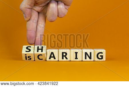 Sharing Is Caring Symbol. Businessman Turns Wooden Cubes With Words 'sharing Is Caring'. Beautiful O