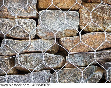 Close-up Fragment Of A Gabion. Stones Of Different Colors, Sizes And Shapes In A Metal Mesh.