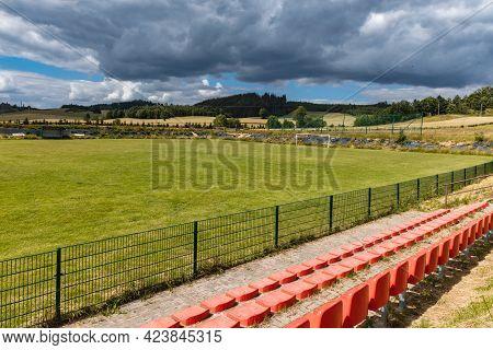 Witkow Slaski, Poland - July 7 2020: Green Football Pitch With Red Plastic Seats Around