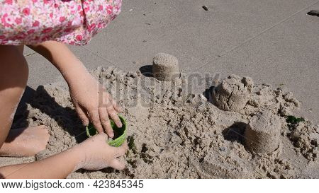Toddler Plays With Sand Molding Toy On Wet Beach Sand By Sea Coastline. Child Makes Sand Molds. Summ