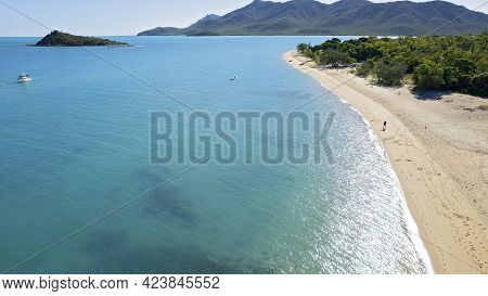 A Man Walking On A Sandy Beach Beside The Clear Blue Ocean With Light Early Morning Light Glistening