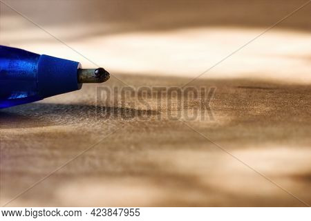 A Micrograph Macro Shot Of A Tip Of A Ballpoint Pen. On The Surface Of The Ball Is Visible Ink And C