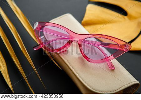 Funky Pink Stylish Sunglasses On Dark Black Background With Gold Palm Leaves. Summer Pink Trendy Gla