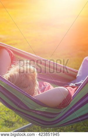 Beautiful Girl Resting In A Hammock At Sunset. Hammock Woman On Blue Background. Happy Spring Day. S