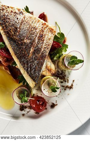 Grilled Seabass With Vegetables With A Brown Crust Top View, Close-up, White Plate.