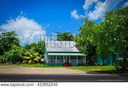 Grand Cayman, Cayman Islands, July 2020, View Of A Popular Style House With A Tin Roof And A Front G