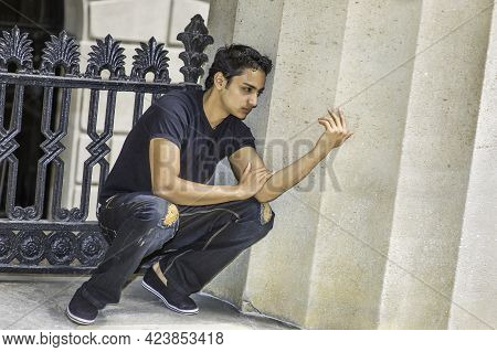 Dressing In Black T Shirt And  A Fashionable Pants, A Young Asian Teenager Is Squatting In The Corne