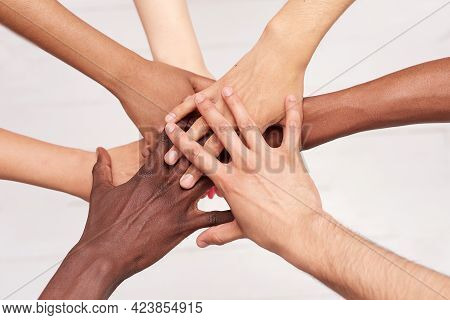 Young People Fold Their Hands. Multinational Friends With A Stack Of Hands Demonstrating Unity And T