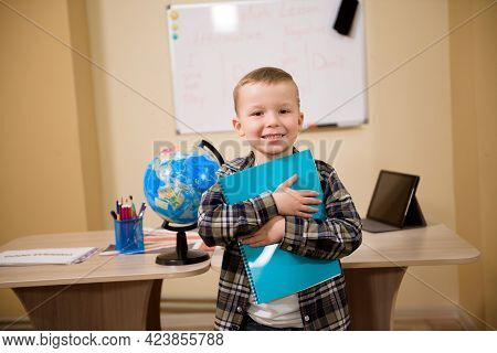 Portrait Of A Boy Looking At Camera In The Classroom.