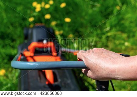Close-up And Selective Focus Of Hand Of Elderly Woman Who Holds Handle Of Lawn Mower. Concept Of Sum