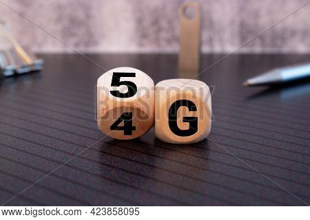 Man's Hand Changing Wooden Block From 4g To 5g On White Surface.