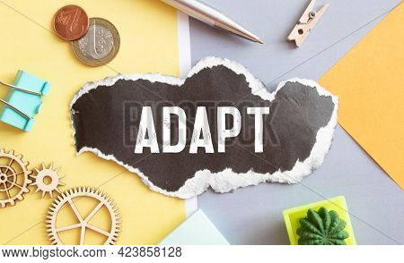 The Word Adapt Wooden Cubes With Burnt Letters, Adaptation In The New Team, Gray Background Top View