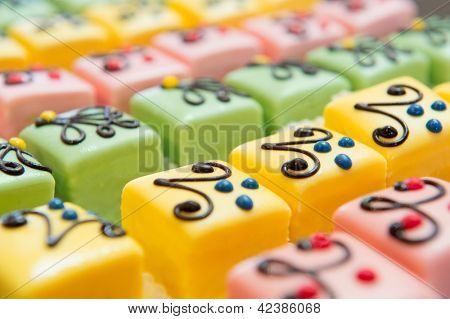 many colorful petit fours with marzipan and chocolate