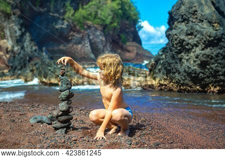 Kid Builds A Cairn Of Stones On The Sea Coast. Beach Games With Children. Leisure In The Evening On