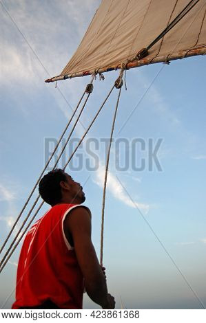 Luxor, Egypt - January 6, 2006: An Egyptian Sailor Operating The Ropes Which Position The Sail On A