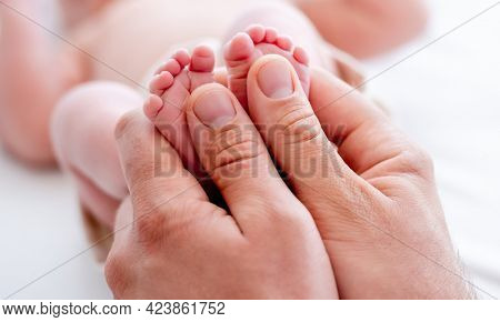 Mother holding tiny newborn baby feet with little fingers closeup. Mom and infant child legs. Concept of matherinity love, care and tenderness