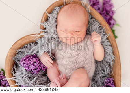 Newborn baby boy wearing knitted beige costume lying in wooden heart shape bed with flowers and sleeping. Adorable infant child napping