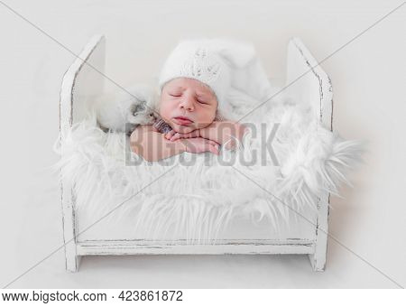 Adorable newborn baby boy sleeping on his tummy in white wooden bed with fur with little fluffy kitten. Cute infant kid wearing knitted hat napping with cat kity during studio photoshoot