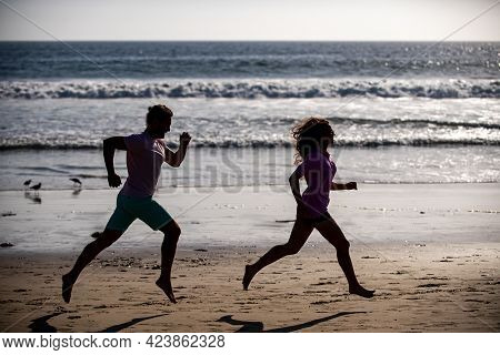 Couple Running On Beach. Sport And Healthy Lifestyle, Silhouette Friends Jogging At Sunset On The Be