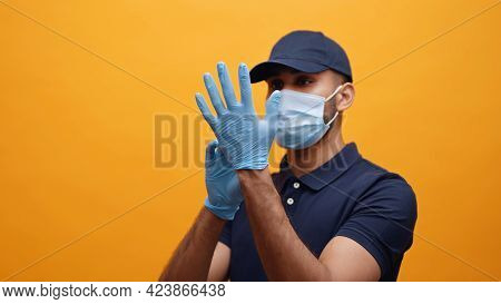 Delivery Man Putting On The Gloves. Wearing A Mask And A Blue Cap Taking Precautions. Concept Of Cov