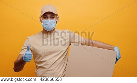 Delivery Boy Wearing Mask And Gloves Holding A Parcel Box And Making Thumbs Up Sign. Concept Of Home