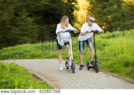 Happy Modern Couple Of Man And Woman Enjoying Eco Ride By Electric Scooter In Sunny Day On Vacation.