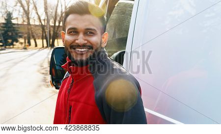 Delivery Guy Standing On The Road Smiling. A White Van Can Be Seen Behind Him. Delivery Guy Wearing