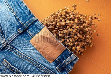 Blue Jeans With A Brown Leather Blank Label And Dry Linen, Close-up. Jeans Texture. Fashion Denim Ba