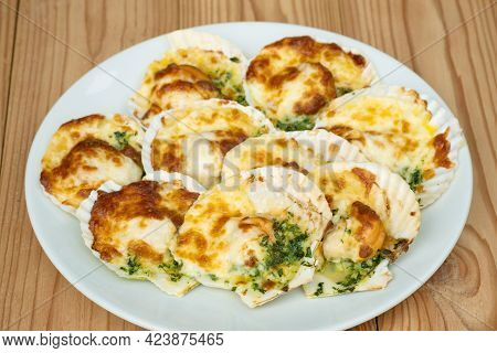 Baked Parmesan Scallops In A White Ceramic Plate On A Wooden Table . Oven Baked Scallop With Cheese,