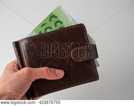 A Man's Hand Holds A Brown Leather Wallet With 100 Euro Bills Sticking Out Of It On A White Backgrou