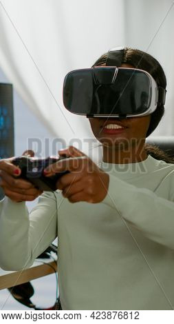 Black Videogamer Woman Winning Space Shooter Game Using Virtual Reality Goggles Playing Games With M