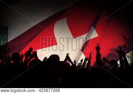 Soccer fans supporting Switzerland - crowd celebrating in stadium with raised hands against Switzerland flag