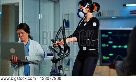 Medical Researcher Using Laptop While Measuring Sportsman Endurance Using Body Sensors, Electrodes A