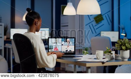 African Employee Working Overtime From Business Office Late At Night Discussing With Partners Online