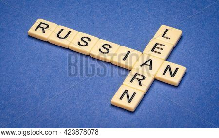learn Russian crossword in ivory letter tiles against blue textured  paper