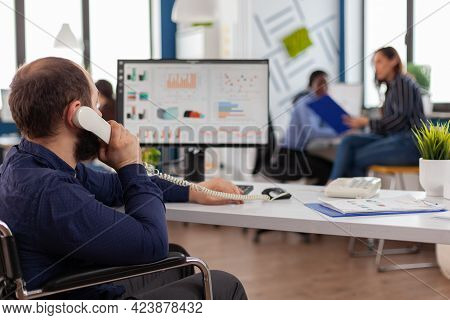 Busy Paralysed Handicapped Team Leader Answering Phone Talking With Partner Typing On Computer Expla