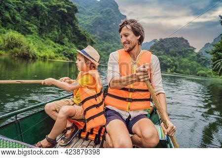 Happy Family Tourists In Trang An Scenic Landscape Complex In Ninh Binh Province, Vietnam A Unesco W