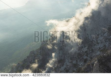 Mountains, Forest, Clouds Top View. Beautiful Airy Transparent Clouds Float Below The Mountains Abov