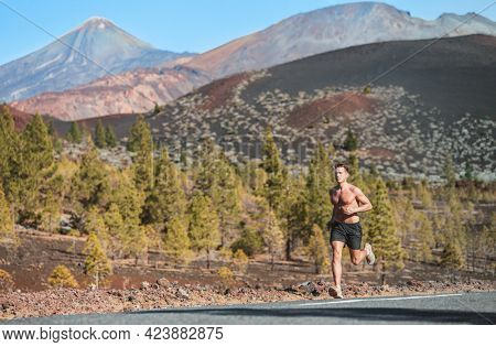 Trail run sport athlete runner man shirtless sweating in summer sun long distance endurance running in volcano mountain forest nature landscape. Summer outdoor training healthy active lifestyle.